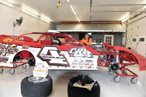 Amanda Whaley poses with her Super Late Model car in her garage.