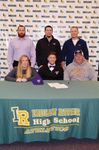 Jacob Anderson, front center, is flanked by his mother, Jennifer Anderson, and father, Joe Anderson. From left in the back row are: football coach Phillip Townsend, brother Joey Anderson and travel baseball coach Marshall Betts.