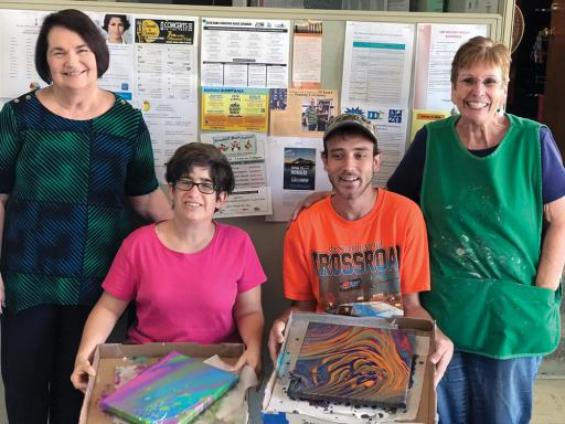 Artist Terry Lake, left, shows off the work of students Jessica Bird, left-center, and Joey Fletcher, right-center, with Creative heARTs assistant program coordinator and art instructor Barbara Buford, right.