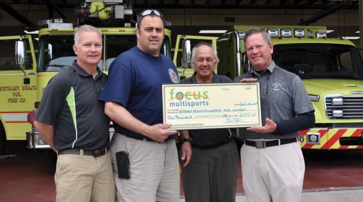 Bethany Beach Volunteer Fire Company Chief Brian Martin, second from left, receives a donation of $2,000 from, from left, Surfin' Snowman organizers Rick Hundley and Ernie Felici of Focus Multisports and presenting sponsor Michael Cummings of Miken Builders.