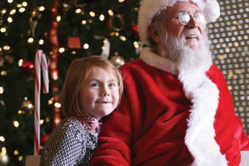 Oliva Brill visits with Santa at a previous Holiday Happening. Last year, all she wanted for Christmas was her two front teeth. We hope she's got them by now!