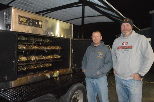 Corrections officer David West and Sgt. Barry Wheatley of the Millsboro Police Department man the rotisserie outside the Millsboro Volunteer Fire Company on Monday, Nov. 25, containing 48 chickens that will be part of meals delivered to first-responders throughout Sussex County on Thanksgiving Day. The meals are provided to police officers, corrections officers, firefighters and other first-responders who are working on Thanksgiving Day.