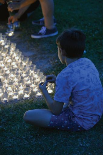 Stephen Urban, 10, of Millville, watches as his parents and others light candles during a July 1 vigil in memory of Linda Bravo, who was missing for two weeks before her body was found on July 28 and her car found July 28 and 29 in a South Bethany canal.