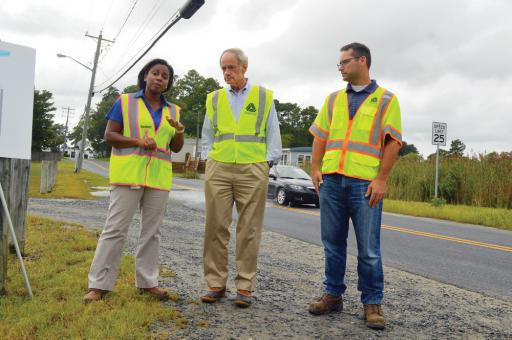 Even as officials discussed the regular flooding of Oak Orchard, cars were driving in the wrong lane in order to avoid giant puddles left from a recent rainstorm and high tide. Pictured, from left, are DelDOT Chief Engineer Shanté Hastings, U.S. Sen. Tom Carper and DelDOT Engineer Jason McCluskey.