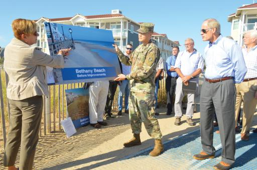From left, Karen McGrath, Lt. Col. David C. Park and Sen. Carper look over a 'before' graphic of the Rehoboth/Dewey Beach replenishment.