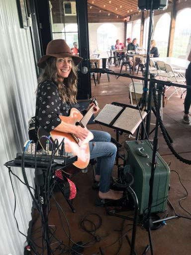Cathy Jane Bostaph plays her homemade suitcase kick drum at Salted Vines Vineyard & Winery.