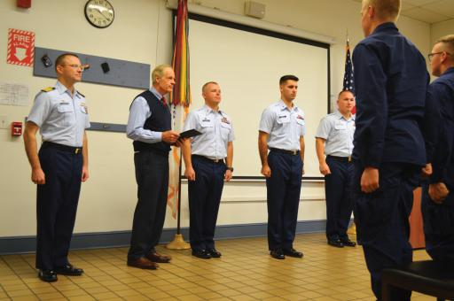 The senator's visit to the Coast Guard station included a quick advancement for a young guardsman, Brennan Piemonte, center-right.