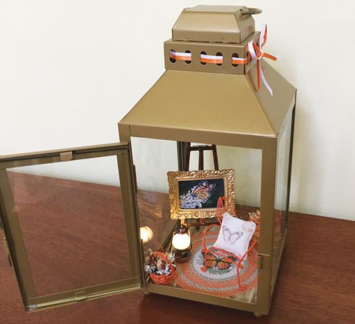 One of the miniature worlds created by local miniature artist Ann Cooper for the debut of her spring and summer 2019 collection at the Ellen Rice Gallery this Saturday, May 4, from 10 a.m. to noon and 1 to 4 p.m. Featured in this lighted lantern is a framed miniature reproduction of Ellen Rice's 'Spread Your Wings' oil painting.