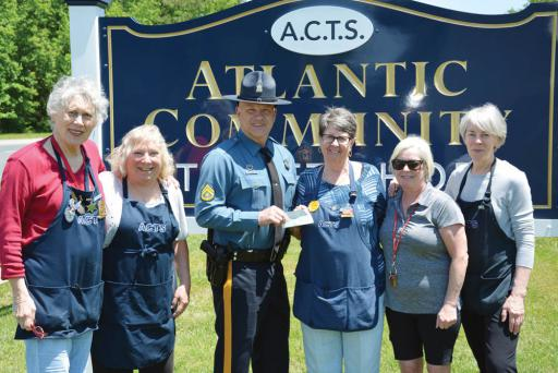 M.Cpl. Shawn Hatfield of the Delaware State Police receives a check donated by Atlantic Community Thrift Store.