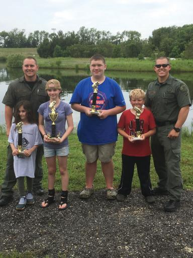 Above the children pose with their trophies from DNREC's Fish & Wildlife Natural Resources Police 32nd Annual Youth Fishing Tournament. From left are: Carly Clevens, first place ages 4-7; Kent winner Adrianna Gott; Trevor Torbert, first place ages 12-15; and Connor Wyatt, first place ages 8-11.