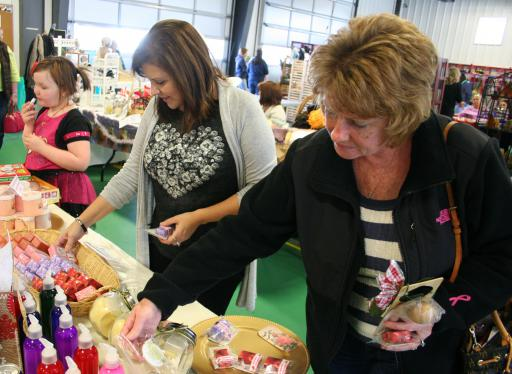 Shoppers Sandy Stewart (right) and Yolanda Nock (center) shop for toiletries while Maya Maine (far left) checks out lip balm at the 2015 Holiday Expo.