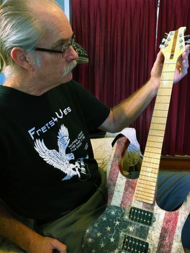 Rob Chadwich shows off his new guitar, handmade and donated by Frets4Vets, after he completed the Frets4Vets program.