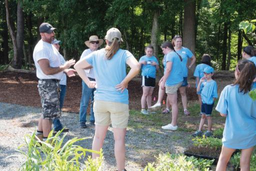 Troop 20566 and adult leaders gather on the Mound in Oudolf Meadow Garden, with their DBG hosts.