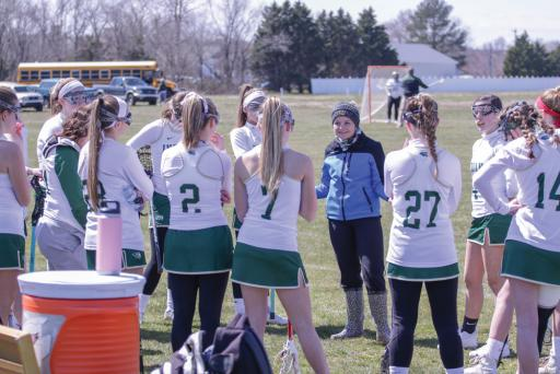 Girls' lacrosse coach Cat Roselli gives a pep talk to her players last season.