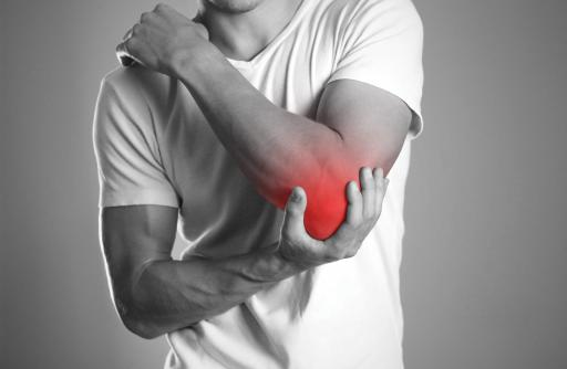 A man in a white T-shirt grasps his elbow, as if in pain. The elbow area is colored red.