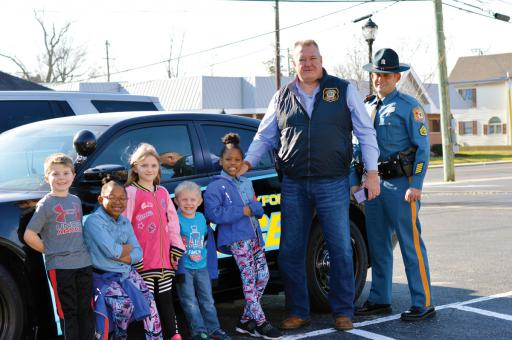 Frankford Police Chief Larry Corrigan hosted a Holiday Lunch for local families on Saturday, Dec. 28 at the Frankford Town Hall. Shown getting their close-up with one of the town police cars, from left, are: Gus Catlin-Brown, Raylyn Brown, Vada Lynch, Wyatt Lynch, Raylya Brown, Chief Corrigan and Master Cpl. William Bant of the Delaware State Police Community Outreach at Troop 4.