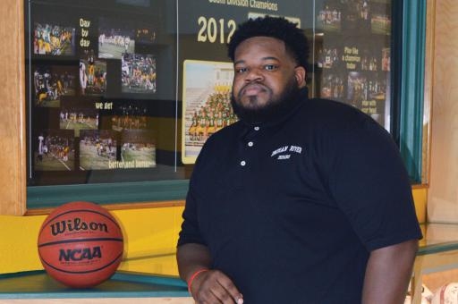 New boys basketball coach Devin Mann poses for a photo in the hallways of Indian River High School.