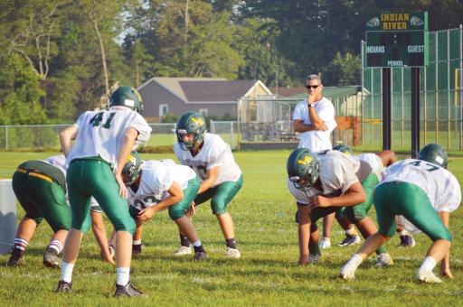 Reese Stone under center during offensive drills as assistant coach Joe Donnelly looks on.