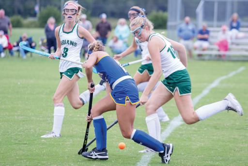 A pair of Indian River field hockey players block an offensive move by an opposing player.