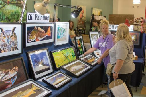 Patrons of the artisan fair at Lord Baltimore peruse a wide selection of oil paintings featuring scenes and wildlife found locally.