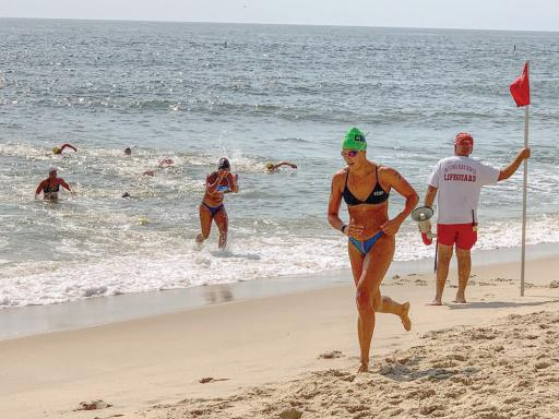Swimmers come in from the ocean during one of the events from the Women's Lifeguard Tournament.