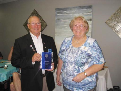 Lion Paul Bolton, left, holds the award after the presentation from Lions President Janet Bauer, right.