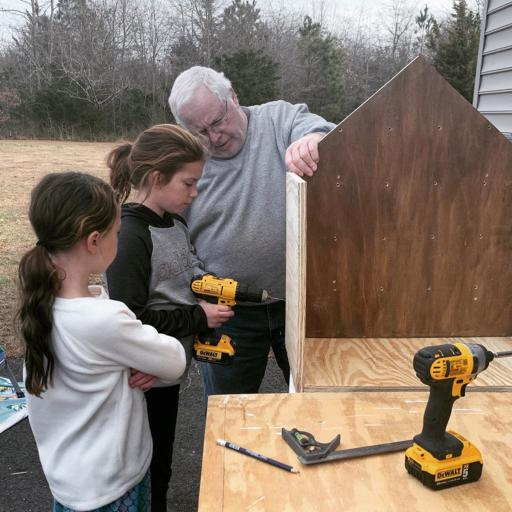 From left, Avery Bare, Maggie Bare and their grandfather, John Dupont, work on the Little Free Library that will soon be a fixture at Ocean View's John West Park.