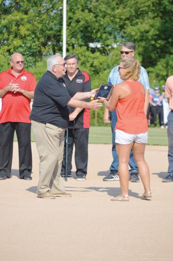 Martin Donovan hands Lauren Weaver, from Bethany-Fenwick Area Chamber of Commerce, a plaque of apprectiation for the Chamber's support of the World Series.