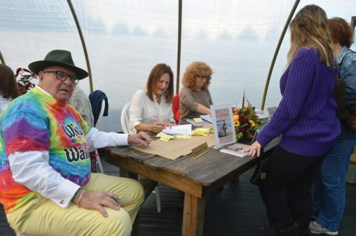 Mary Cannon, center, signs copies of the book 'Willy's Neighborhood' at a recent event at Bearhole Farms in Bayard, celebrating the book and the community that rallied around Cannon and her family when her late husband, Willy Cannon, was diagnosed with ALS. At her right is Bruce Hobler, who wrote the book and who read to Willy Cannon in the last several years of his life. At her left is book publisher Lois Hoffman.