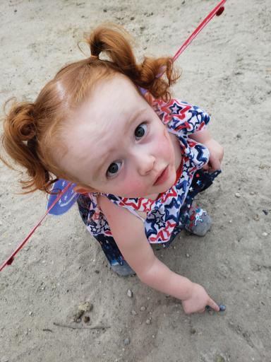 Raven Holbrook, 2, of Berlin, dressed as a patriotic butterfly, draws in the sand at Cupola Park at Millsboro's Stars & Stripes Fireworks. She was there with her mother, Brittnay Lewis.