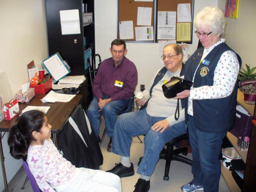 Student Emily Elvira-Rodriquez gets her vision checked by Lions Buck Godwin, Vince Sanzone and Pat Sanzone.