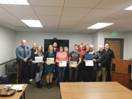 A Millsboro officer poses for a photo with graduates of their Business Academy on Tuesday, Nov. 13.