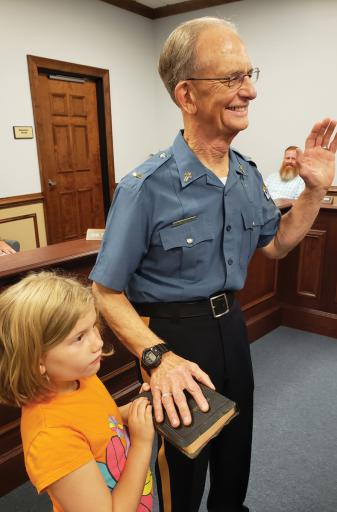 The Millsboro Police Department swears in the Rev. Rod Dufour as its new police chaplain, while Dufour's granddaughter Claire holds the Bible for the ceremony. Dufour is also the father of MPD officer Matthew Dufour.
