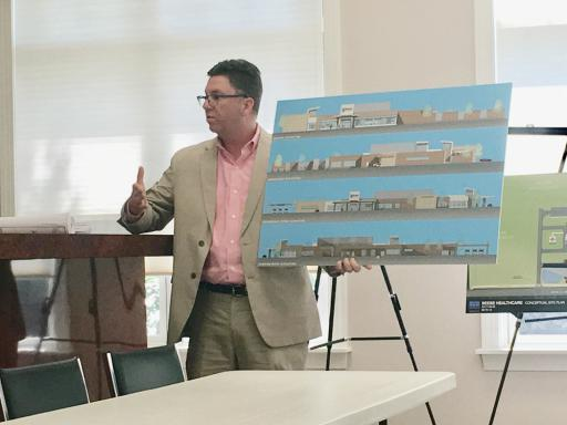 Jeffrey Harman of the Becker Morgan Group holds a rendering of the exterior of Beebe Medical Center's proposed Millville campus at a Friday, Aug. 17, public hearing on the project.