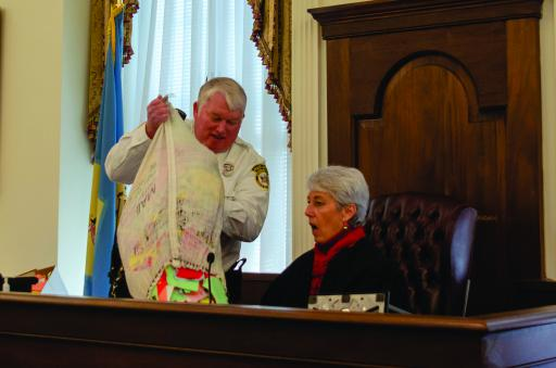 Bailiff Tony Summers presents Superior Court President Judge Jan R.Jurden with a satchel full of letters addressed to Santa Claus during the competency hearing for one Kris Kringle.