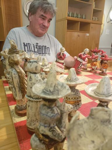 ouse of Modern Living owner Bill Miesch holds pieces of the chess set made from paper mache.