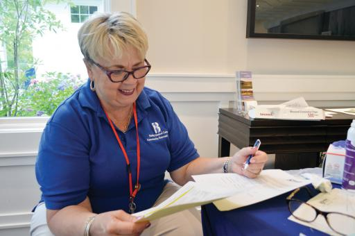 Beebe Nurse Ronni Smith laughs while telling a reporter to exercise more, as she administers health screenings at the Bayside Institute's Wellness Week.