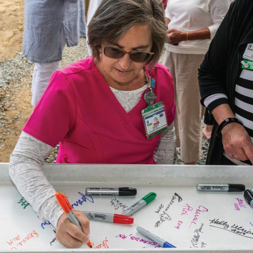 Nurse Sherry Daisy signs the beam at Beebe Healthcare's South Coastal Health Campus on Thursday, June 13.