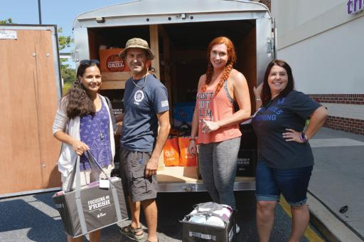 Gathering by a trailer they helped load with goodies for this year's Operation SEAs the Day participants are Warrior Week alumni, from left, Omy Emami, Nima Emami, Jonell Gottlieb and Sara Klopfenstein. Along with Operation SEAs the Day volunteers, they packed bags and boxes at the Giant supermarket in Millville on Monday, Sept. 3.