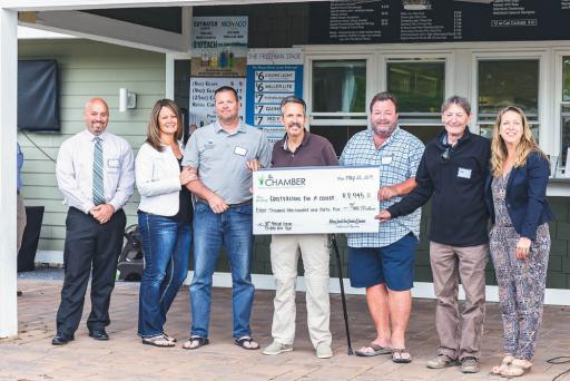 Cory Walsh, president of the Bethany-Fenwick Area Chamber of Commerce, left, and Lauren Weaver, executive director of the Chamber, right, present a donation from the Quiet Resorts Charitable Foundation to representatives of Contractors for a Cause, including, from left, Karen Coleman, Chuck Coleman, Brian Hinds, Garth Troescher and Ted Stevens.