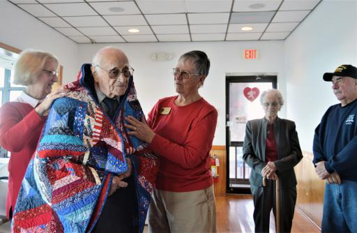 Dana Mason of the Quilts of Valor Foundation, left, reads a tribute to quilt recipient Charles Marvel at a ceremony on Feb. 9 at the Mason Dixon Post 7234 in Ocean View. Looking on are Marguerite Neimoller of the Foundation, holding his quilt; Marvel's wife, Irene, and Post 7234 Commander Dean Levering.