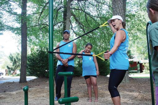 Kim Royster demonstrates an exercise at South Bethany's new fitness area, while her husband and daughter, Mel and Tory, look on.