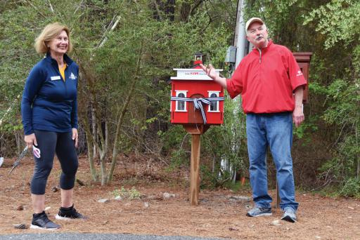 Frank Weisberger stands with the Little Free Library he carved, alongside South Bethany Councilmember Sue Callaway.