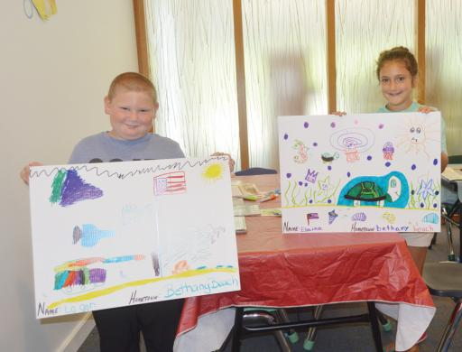 Logan Andrea, 6, and Elaina Andrea, 8, of Bethany Beach, show off the posters they created at a Poster Pal event Tuesday, July 9, at the South Coastal Library in Bethany Beach.