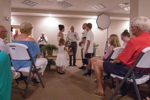 Retired U.S. Marine Greg Gerard, his fiancée, Amber Falck, and family tie the knot at the Edgewater House community room at Sea Colony during Operation SEAs the Day.