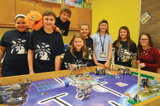 The Selbyville Middle School Lego Robotics Team poses for a photo with their Lego robots.