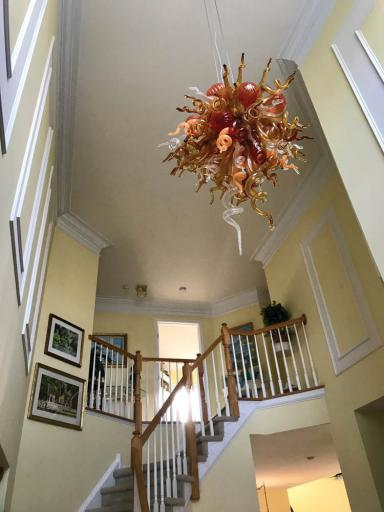 A whimsical glass chandelier graces the stairway of this treasure-filled home.