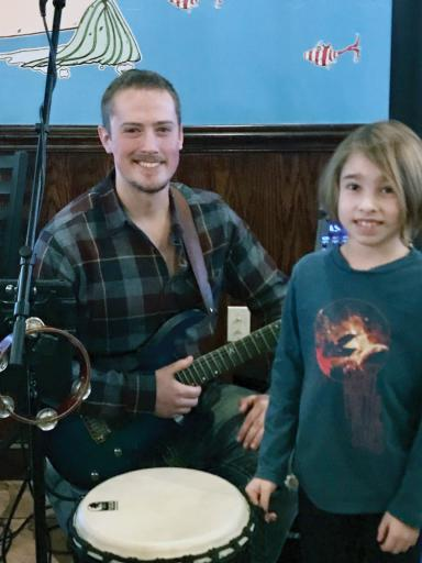 Local musician and music teacher Taylor Knox visits with student Lucas Bennett during Knox's regular Friday-night gig and open-mic at Hooked Up in Millville. Knox is also part of the local reggae-rock band Human Connection, and is now shepherding the Taylor Knox Project as that progressive-rock trio brings its original songs to local venues.