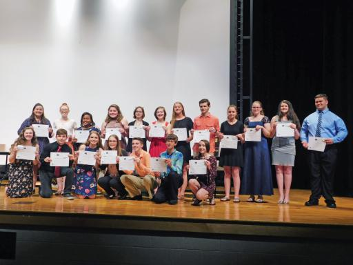 Members of the first Tri-M Music Honor Society group in at least 30 years pose for a photo on stage.