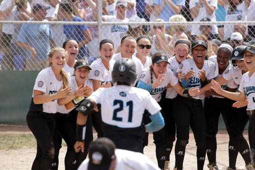 Jakayla Sample runs in to homeplate after hitting a homerun, with her team gathered to celebrate.